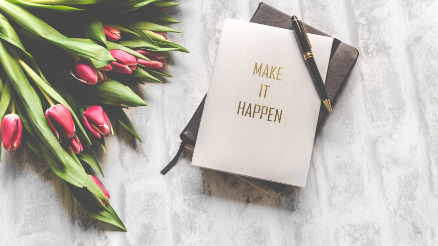 "Flowers and notebook that reads ""make it happen"""