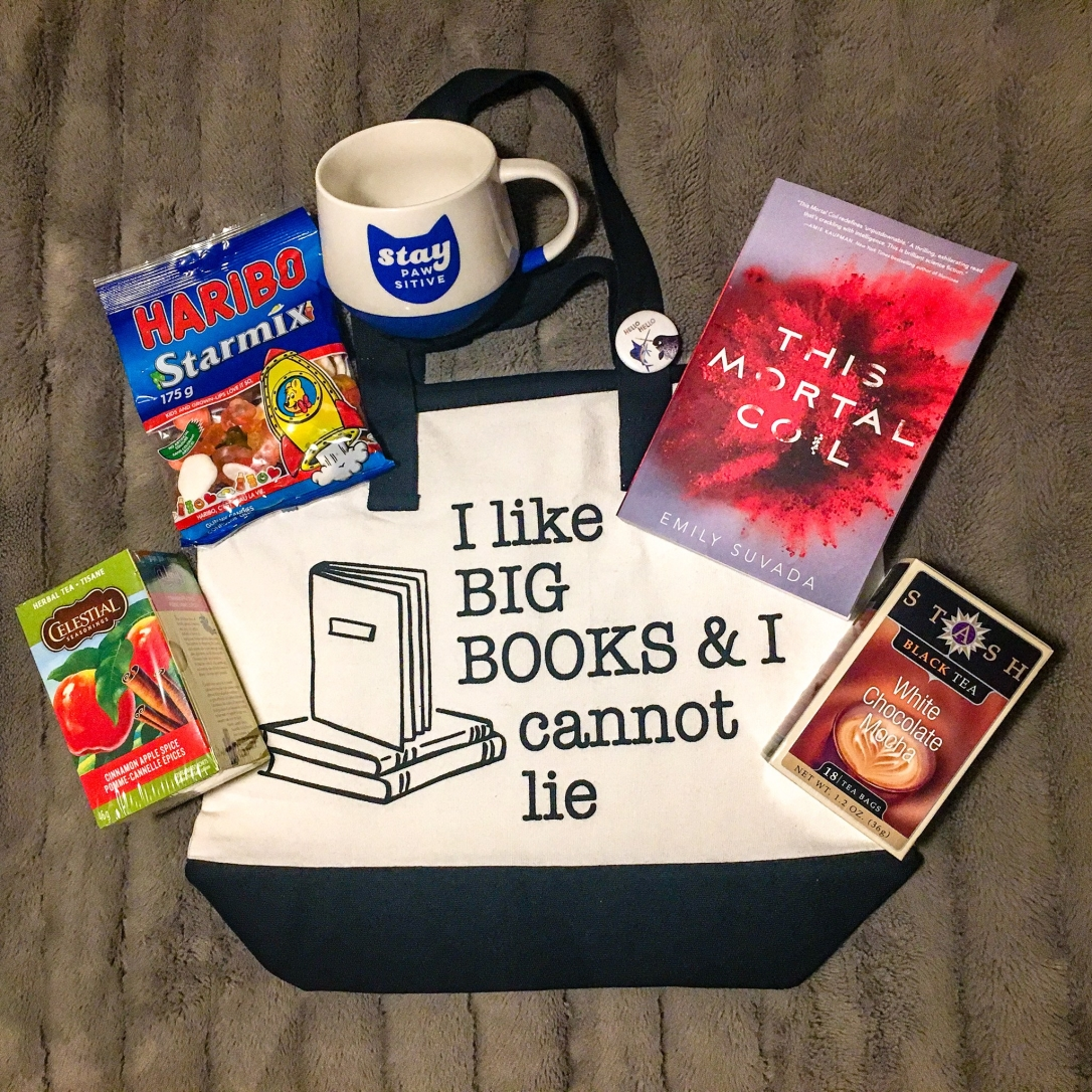 "Gift basket: white mocha tea, apple and cinnamon tea, ""Stay Pawsitive"" mug, a gummy mix, This Mortal Coil by Emily Suvada, ""I Like Big Books and I Cannot Lie"" tote, ""Hello Hello"" narwhal pin"