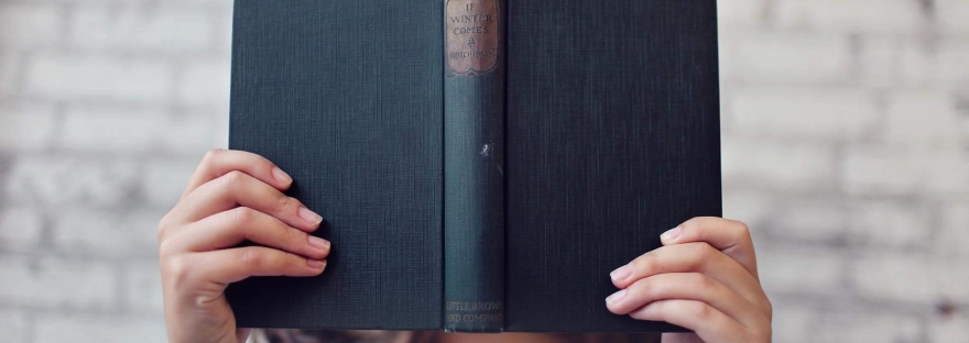 A woman alone holding a book in front of her face