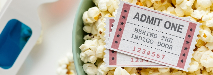A bowl of popcorn with two movie tickets next to 3D glasses